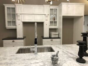 Kitchen cabinetry with granite and marble counters