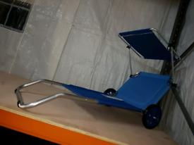 A new stylish blue folding light weight sun lounger on wheels .