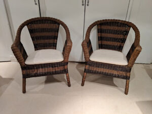 Pair of wicker chairs with cushions.