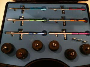 Airbrush set with six airbrush's , hose and holder.