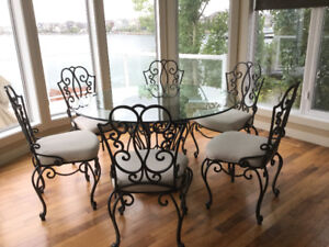 Large glass and rod iron kitchen table and six rod iron chairs