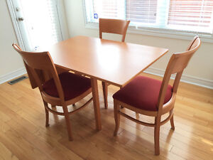 Dining table with a drop-leaf and four chairs.
