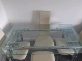 Large glass dining table with chairs