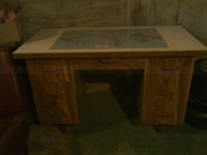 Student desk with world map print on surface