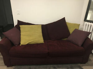 Purple couch with pillows in good condition.