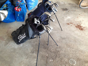 Two golf bags with a mix of newer and older clubs