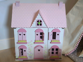 Wooden doll house with furniture and dolls.
