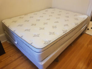 Queen sized bed with metal bed frame and box spring