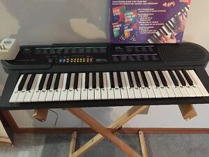 Concertmate 690 Keyboard with stand and books.