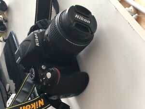 Brand New Nikon D5200 with 18-50mm lens and a camera bag.