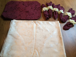 Table clothe with 5 burgundy placements and napkins with flower