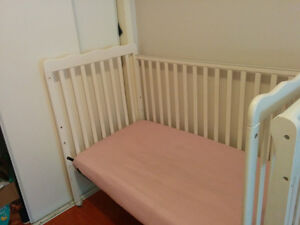 White beautiful crib with convertible toddler bed railing