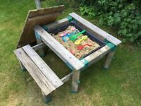 Children's play sandpit with bench seat and sand and toys