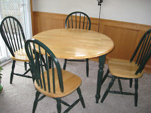 Round wooden table with four chairs
