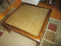 Square wooden coffee table with rattan inlay under glass top