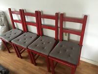 4 red chairs with grey cushions
