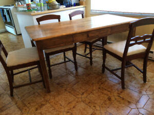 Solid wood table with drawer and 4 upholstered chairs.