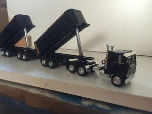 1-64 scale white freight liner C/O hauling A train dumps.