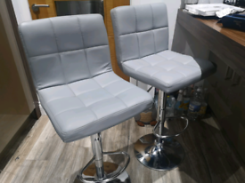 2 grey faux leather bar stools