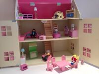 Pink wooden dolls house complete with furniture and dolls