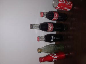 Coke bottles mostly full ones with an arabic coke can full