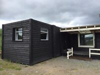 Portacabin 30'x10', part clad with pine stained black, one room. Inverness.