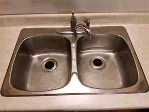 Stainless steel sink with delta faucet.