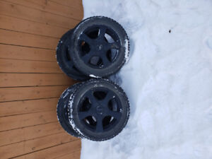 set of four studded winter tires with rims and spacers