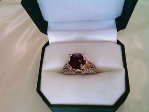 One lady's 14k rose gold, garnet and diamond ring.