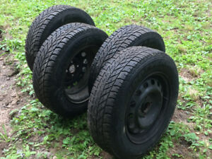 4 Goodyear Ultragrip studded winter tires with rims. 185/70R14