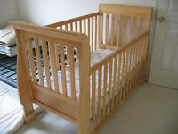 Light brown wood crib with mattress and 2 yellow covers