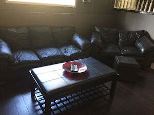 Black leather couch, love seat, coffee table and ottoman set