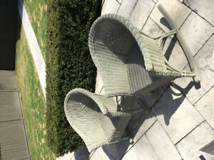 2 antique wicker rocking chairs with seat cushions.