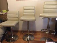Three cream faux leather stools.