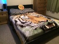 Kingsize black leather frame bed.