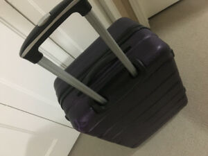 Large, dark purple suitcase. Used once