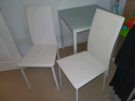 2 white chairs and glass dining table