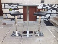 Chrome/glass bar style table and 2 chairs/stools.