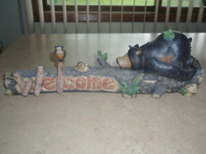 BEAR FIGURINE LYING ON A WELCOME LOG