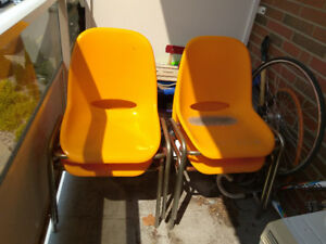 Four orange plastic stacking chairs