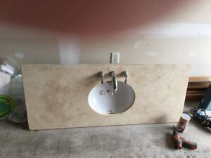 Quartz vanity top with sink and faucet.
