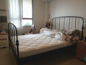 Queen-size metal bed frame with mattress and pad