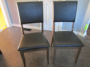 Tow faux black leather and walnut wood chairs