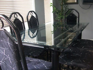 glass top dining table mounted in a steel black frame with six b