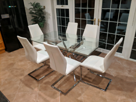 large glass dining table with chrome legs and 6 white leather chairs