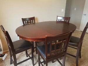 Large dining table with 5 matching chairs and 2 extra stools