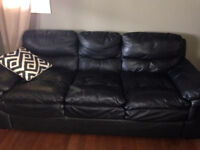 Black leather sofa with 2 pillows