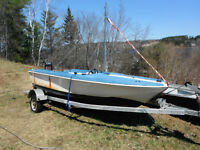 fiberglass wakeboard boat with 40 hp on galvanized trailer.