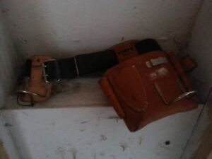 A Tool Belt With Two Hammer Holders And Leather Pouch.