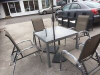 Brand New 4 Seater Metal Outside Table With Glass Top With 4 Metal Reclining Chairs And Parasol